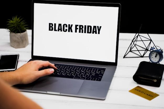 Mão na palavra-chave do laptop e área de trabalho preta de sexta-feira