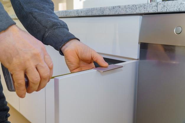 Mão na porta de instalação de alça no armário de cozinha