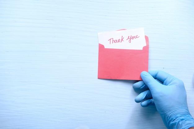 Mão nas luvas protetoras segurando uma carta de agradecimento.