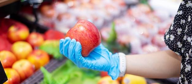 Mão nas luvas segurando uma maçã