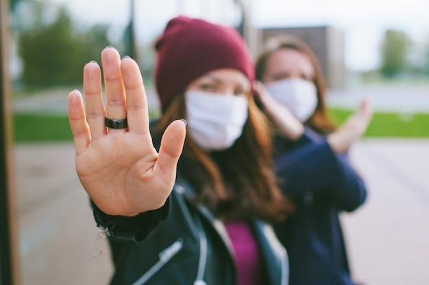 Mão no close-up da câmera, fêmea com máscaras médicas. contra o pano de fundo de um edifício de vidro. conceito de parada de vírus.