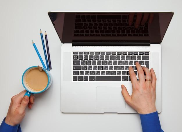 Mão no teclado do laptop e mão com uma xícara de café