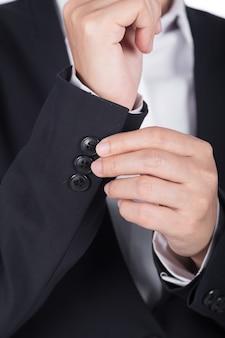 Mão no terno preto é vestir-se