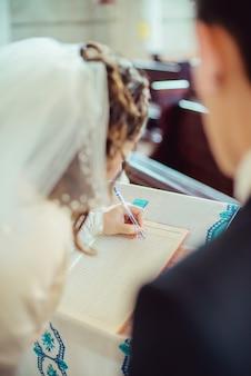 Mão noiva, com, um, caneta, assinando, licença casamento