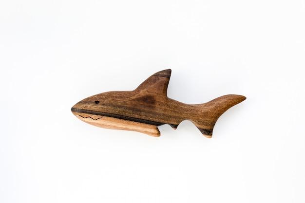 Mão orgânica feita de madeira tubarão brinquedo isolado no branco