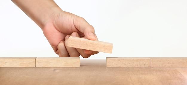 Mão organizando bloco de madeira e sucesso de crescimento do conceito de negócio