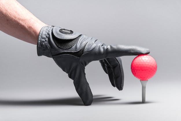 Mão organizando bola de golfe