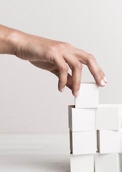 Mão organizando cubos brancos
