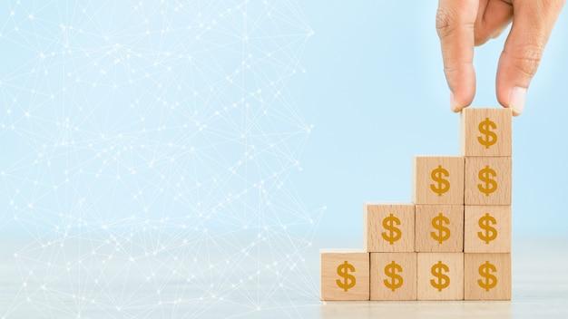 Mão, organizando o bloco de madeira com dinheiro dólar ícone para o conceito de investimento