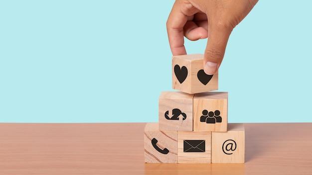 Mão organizando o bloco de madeira com o contato do ícone. mente de serviço ao cliente e conceito de contato de serviço de suporte ao cliente. copie o espaço