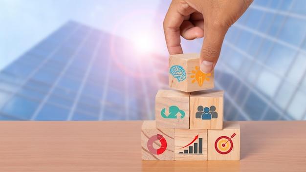 Mão organizando o bloco de madeira com plano de ação e estratégia de negócios de ícone. objetivo e objetivo, conceito de objetivo e objetivo de negócio, gestão de projetos, desenvolvimento de estratégia da empresa. copie o espaço.