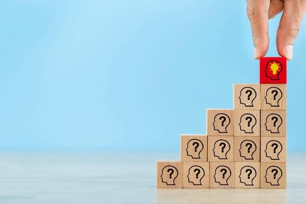 Mão, organizando o bloco de madeira com símbolo humano da cabeça ícone e lâmpada. idéia criativa do conceito e inovação.