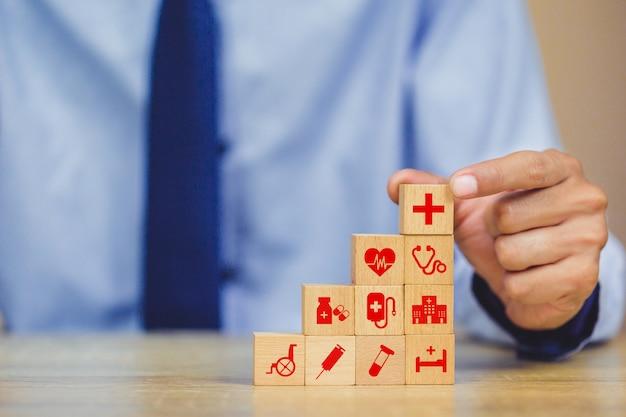 Mão organizando o bloco de madeira de empilhamento com ícone de saúde médico.