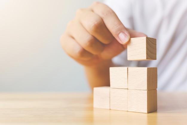Mão, organizando o bloco de madeira que empilha como escada em cima. processo de sucesso nos negócios