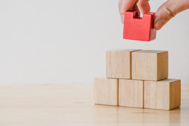 Mão organizando o bloco de madeira