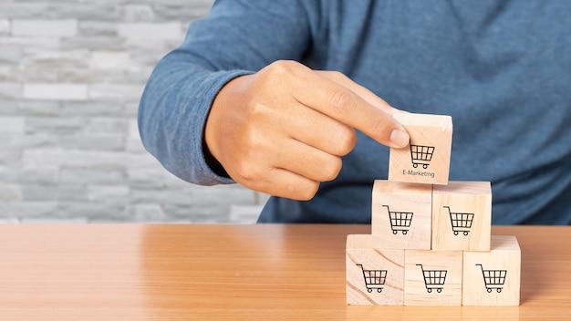 Mão organizando o cubo de madeira empilhando com o ícone gráfico e o símbolo do carrinho de compras. processo de sucesso de crescimento do negócio. conceito de negócios. comprar online. e-marketing.