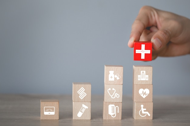 Mão organizando o empilhamento de blocos de madeira com ícone de saúde médica Foto Premium