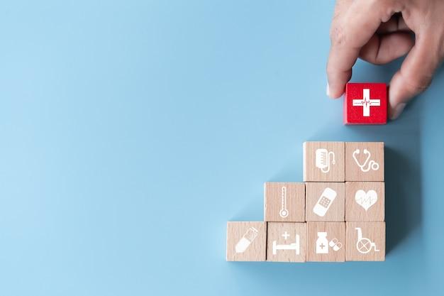 Mão organizando o empilhamento de blocos de madeira com ícone de saúde médica