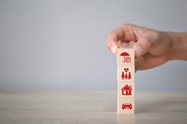 Mão, organizando o empilhamento de blocos de madeira com seguro de ícone: carro,