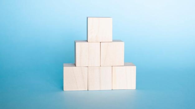 Mão organizando o empilhamento de cubos de madeira como escada. conceito de negócios