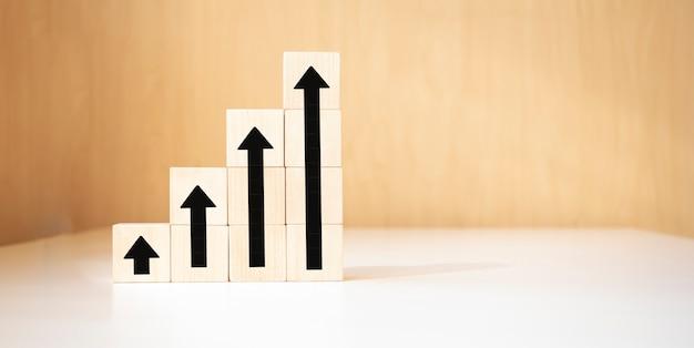 Mão organizando o empilhamento do bloco de madeira como escada de degraus com a seta para cima. conceito de plano de carreira de escada para o processo de sucesso de crescimento do negócio