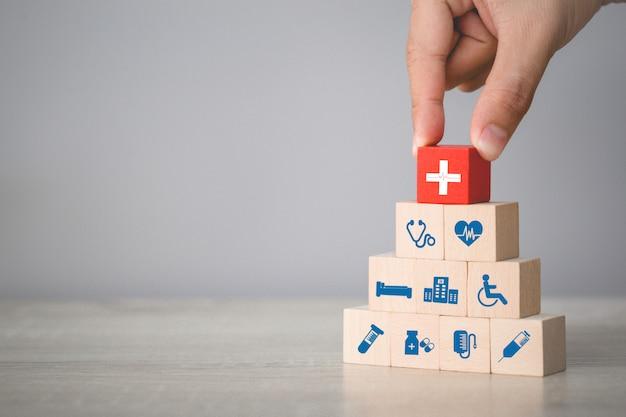 Mão, organizando os blocos de madeira de empilhamento com ícones de saúde e médicos