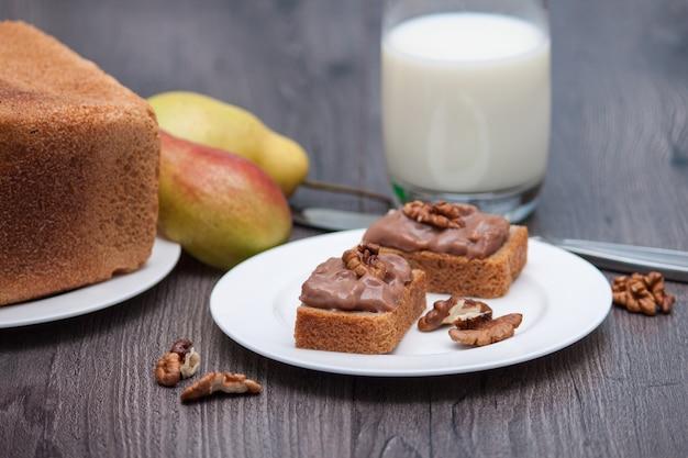 Mão ou pasta de chocolate caseira com nozes. lanche saudável. leite, pêra, pão.