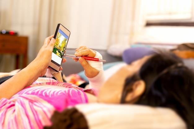 Mão paciente sênior ferida com a atadura que encontra-se para baixo e que usa o telefone celular.