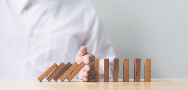 Mão para o efeito dominó de madeira da crise do negócio ou proteção contra riscos