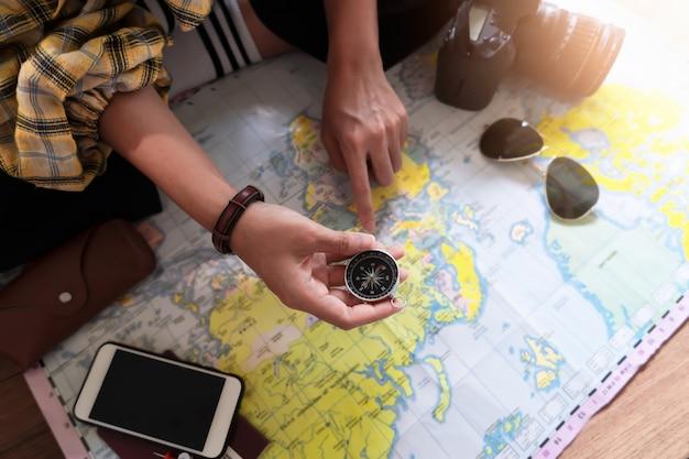 Mão para planejar viagem de férias e acessórios para viagem