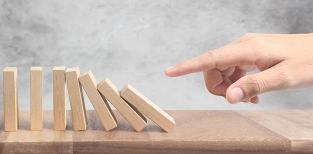 Mão parando efeito domino interrompido por exclusivo