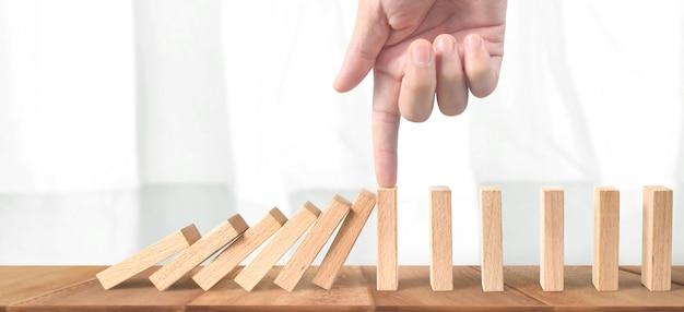 Mão parando o efeito domino interrompido por exclusivo
