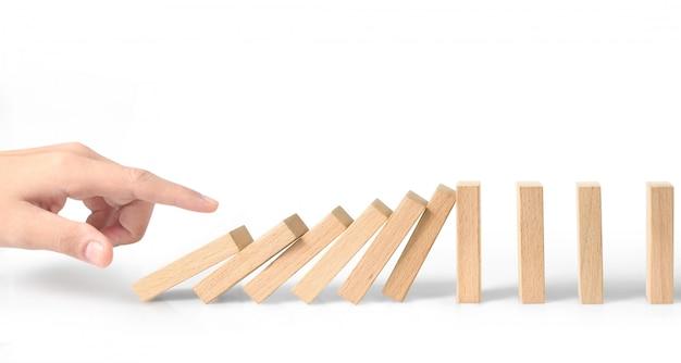 Mão parando o efeito domino interrompido por um único