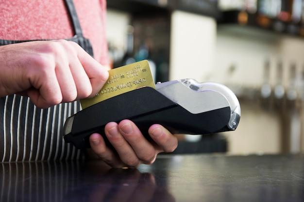 Mão passando o cartão de crédito no dispositivo de leitura de cartão