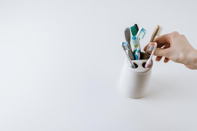 Mão pega escova de dentes ecológica de um copo branco