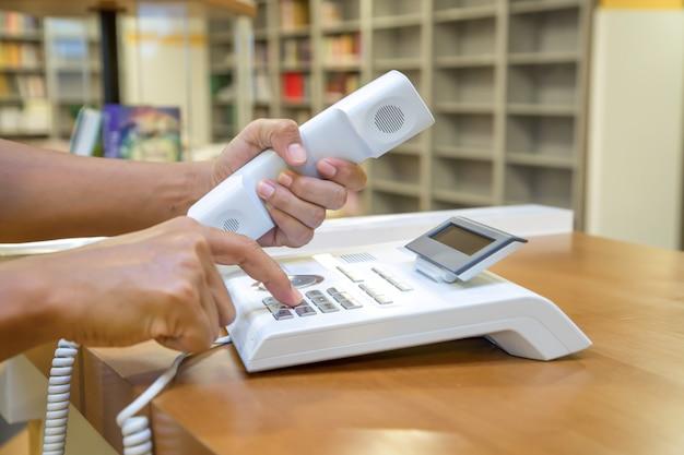 Mão pega o telefone e pressiona o botão