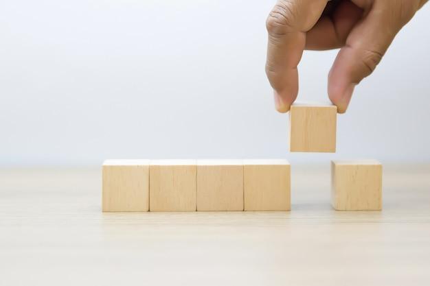 Mão pegando bloco de madeira com gráfico fora.