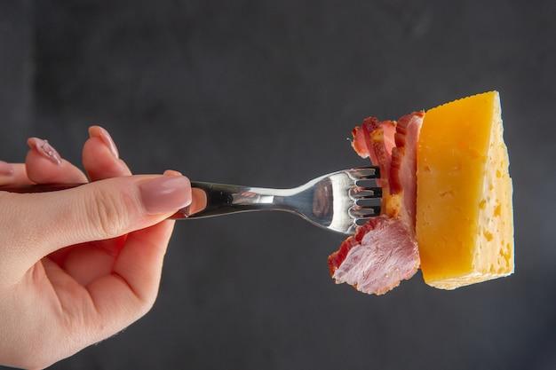Mão pegando com um garfo uma deliciosa fatia de salsicha e queijo em um fundo escuro