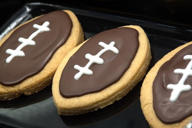 Mão pegando o biscoito do prato. cookies de forma de futebol no prato. conceito de biscoitos caseiros. conceito de esporte americano. cookies de festa do super bowl.