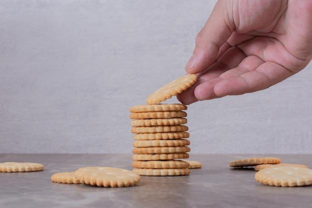 Mão pegando um dos biscoitos na mesa branca.