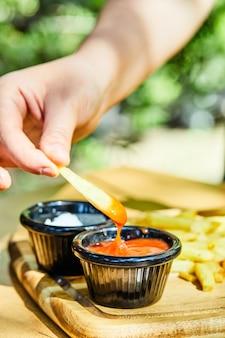 Mão pegando um pedaço de batata frita com ketchup na mesa de madeira.