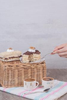 Mão pegando um pedaço de bolo na mesa branca.
