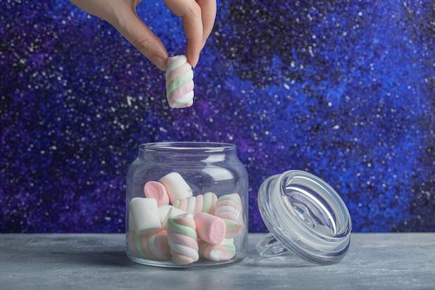 Mão pegando um pedaço de marshmallow macio do frasco de vidro.
