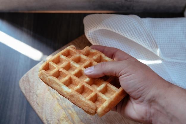 Mão pegando um waffle do prato