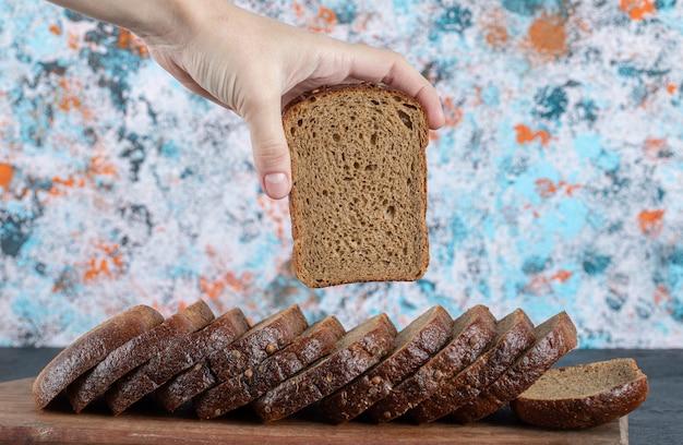 Mão pegando uma fatia de pão fresco na placa de madeira.