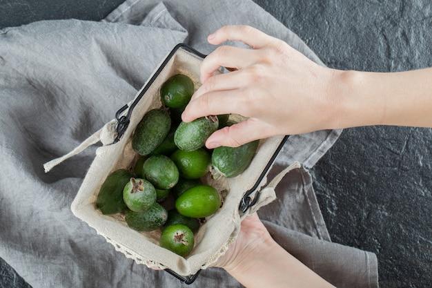 Mão pegando uma feijoa da cesta em uma toalha de mesa cinza