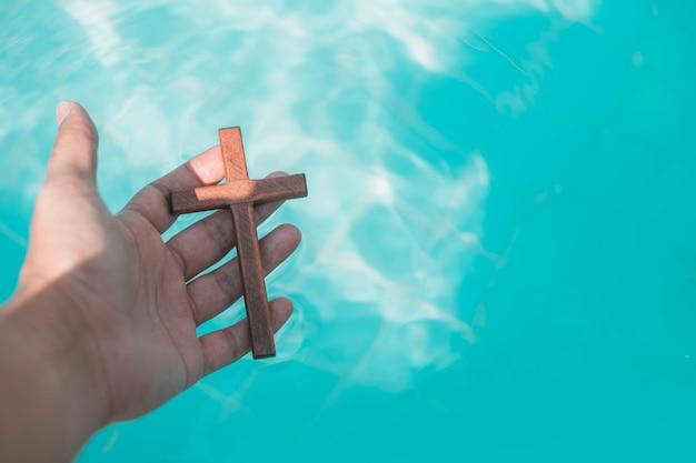 Mão pegar uma cruz de madeira da água.
