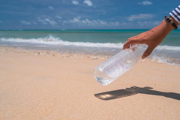 Mão pegar uma garrafa de água vazia ou lixo na bela praia. meio ambiente questão de aquecimento global.