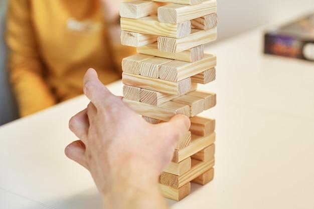 Mão, pegue a um quarteirão da torre de madeira no jogo de tabuleiro de entretenimento familiar com fundo branco