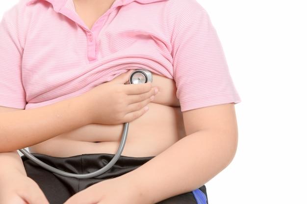 Mão pequena verificar coração pelo estetoscópio para menino asiático obeso